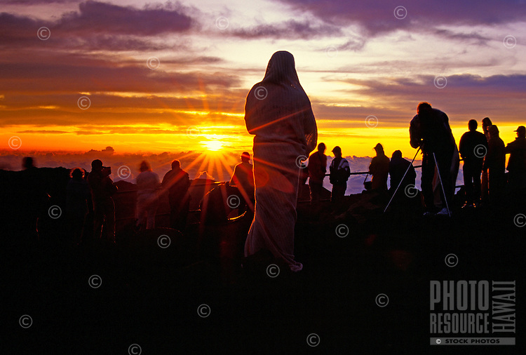 A woman in a blanket enjoys sunrise the main visitor center at a 9,745-ft. elevation in the Haleakala National Park.