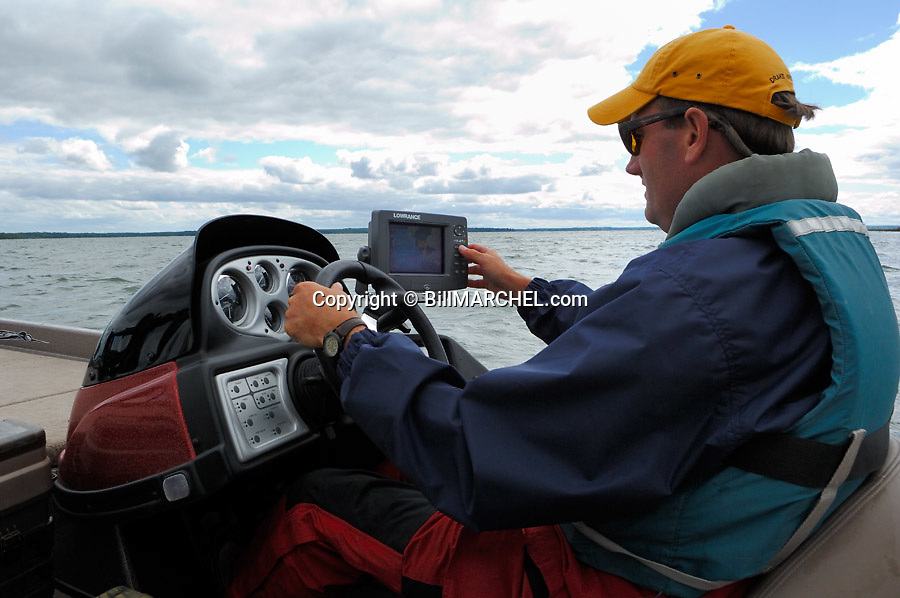 00416-027.14 Fishing: Angler is driving bass boat on cool, cloudy day.  Note electronics.  Wind, clouds, cold front, life jacket.  H6L1