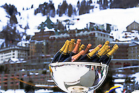 Bottles of champagne in ice bucket awaiting winners of Ice Polo Match against large hotel in background