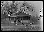 THE SHELBY HOUSE, 924 PLUM STREET. James Shelby (1874-1930) and his wife, Mary, stand at the front of the house they purchased in 1912 for a hard-earned $1,800. He worked as a hotel porter, waiter, and eventually headwaiter. She was a dressmaker and a Sunday school teacher at Quinn Chapel. In the early 1920s, James was proprietor of a downtown restaurant. Later in the decade he owned Union Hat Company, offering shoe shining and hat blocking.<br /> <br /> Photographs taken on black and white glass negatives by African American photographer(s) John Johnson and Earl McWilliams from 1910 to 1925 in Lincoln, Nebraska. Douglas Keister has 280 5x7 glass negatives taken by these photographers. Larger scans available on request.