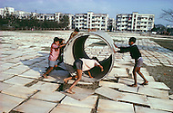 January 1979, Calcutta, India.  Outside Calcutta, children use heavy and large cement drainage pipes to flatten pieces of wood to make plywood - Child labor as seen around the world between 1979 and 1980 - Photographer Jean Pierre Laffont, touched by the suffering of child workers, chronicled their plight in 12 countries over the course of one year.  Laffont was awarded The World Press Award and Madeline Ross Award among many others for his work.