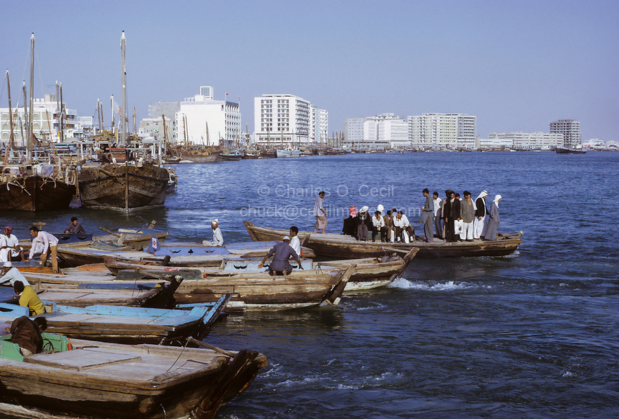 Dubai 1972, United Arab Emirates.  An Abra (Water taxi) Crossing The Creek.  National Bank of Dubai left of center (with flag); Apartment and Office Buildings in the Background.