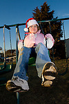 Little Girl playing outside dressed in a Christmas Hat