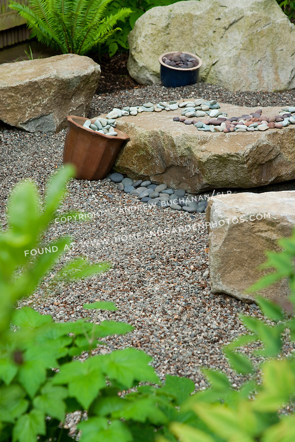 A path leads to an interactive stone display in the corner of this garden.