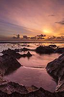 At sunset, water swirls around tide pool rocks at Shark's Cove, North Shore of O'ahu.