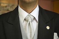 Switzerland. Canton Graubünden. St. Moritz. Hotel Carlton. Butler. Matheus Alcover wears a Matrix tie's knot.  © 2008 Didier Ruef