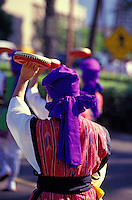 Rear shot of two Okinawan women with purple head scarves and traditional ikat vests march in the Okinawan Festival Parade with tambourines held above them.