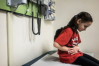 Beatrice Lipp sits on an examination bed. She is an 8 year old with ulcerative colitis, a form of inflammatory bowel disease (IBD) which causes inflammation and ulcers in the colon. She has been in and out of Hospitals for the last 5 years.  Now at Boston Children's Hospital, she is part of a social robotic experiment between Boston's Children Hospital and the Massachusetts Institute of Technology (MIT). The goal of the experiment is to determine whether a so called 'Huggable' teddy bear, a social robotic stereotype, can have therapeutic value for children who have to endure long hospital stays. The bear's talking and movements are remotely controlled by Hospital Staff from outside of the room.