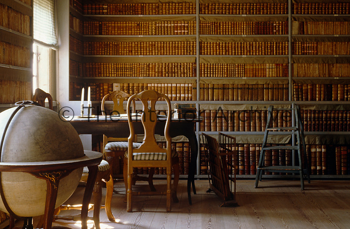 A globe stands in the corner of this library with walls lined with leather-bound books