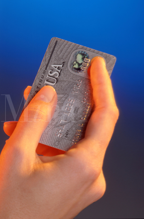 A hand holding a credit card.