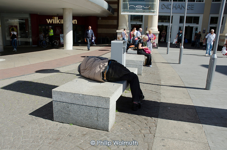 A man sleeps on a bench in a shopping centre in Ilford, Essex