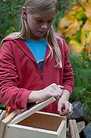 Mädchen baut einen Vogel-Nistkasten aus Brettern, 7. Schritt: zu öffnende Vorderseite einsetzen