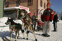 Diana Moroney's wheel dogs Victor (L) and Scooby-Do lunge to go as Diana comes off her 24-hour layover at the Tokotna checkpoint.  2005 Iditarod Trail Sled Dog Race.