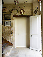 A horn that belonged to Gerard Tremolet's grandfather and an antique hunting trophy hang above a door in the back staircase hall