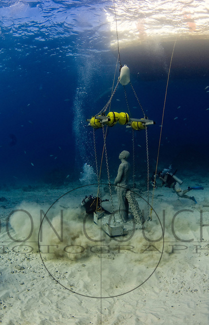 Touchdown - the first of over four hundred sculptures by artist jason deCaires Taylor is lower to the sea floor in the waters off Cancun, Mexico. Envisioned as both a major tourist attraction and an artificial reef, when completed in december 2010, it will become the world's largest underwater museum.