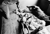 """USA. New York City. Spanish Harlem. Puerto Rican family.  Carlos (L), his brother Papo (C) and their cousin Richie (R) play on the bed in the sleeping room. The family lives below the poverty line and receives public assistance (AFDC, Home Relief, Supplemental Security Income and Medicaid). The family resides in units managed by the New York City Housing Authority (NYCHA) which provides housing for low income residents. NYCHA administers rental apartments in facilities, popularly known as """"projects"""". Spanish Harlem, also known as El Barrio and East Harlem, is a low income neighborhood in Harlem area. Spanish Harlem is one of the largest predominantly Latino communities in New York City. 15.10.86 © 1986 Didier Ruef"""