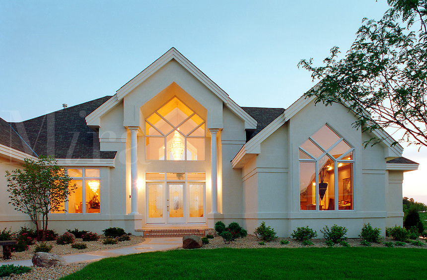 The exterior front entryway and residential wing of a contemporary executive style home with the lights on at dusk.