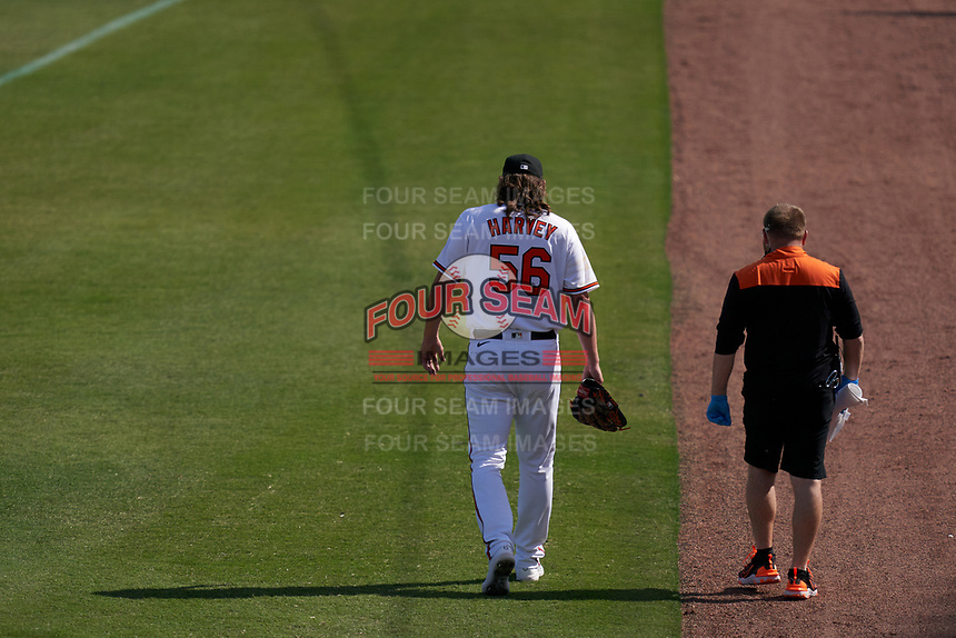 Baltimore Orioles pitcher Hunter Harvey (56) leaves the field with the training staff after being injured after one pitch during a Major League Spring Training game against the Philadelphia Phillies on March 12, 2021 at the Ed Smith Stadium in Sarasota, Florida.  (Mike Janes/Four Seam Images)