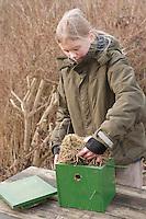 Nistkasten, Mädchen, Kind reinigt Vogel-Nistkasten und entnimmt altes Nistmaterial