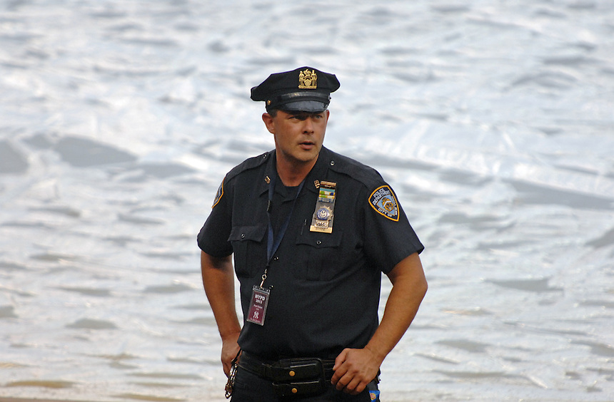 A NYPD officer keeps an eye on the crowd during a rain delay at Yankee Stadium. MARK TAYLOR GALLERY.