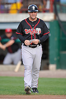 Manager John Tamargo Jr. #25 of the Lansing Lugnuts walks to the home plate meeting prior to their game against the Burlington Bees at Community Field on July 28, 2014 in Burlington, Iowa. The Lugnuts won 9-2.   (Dennis Hubbard/Four Seam Images)