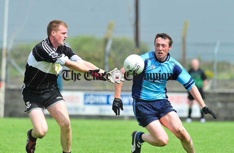 Frank O' Dea of Doonbeg takes posession ahead of Cooraclare's Pauric Looney. Photograph by Declan Monaghan