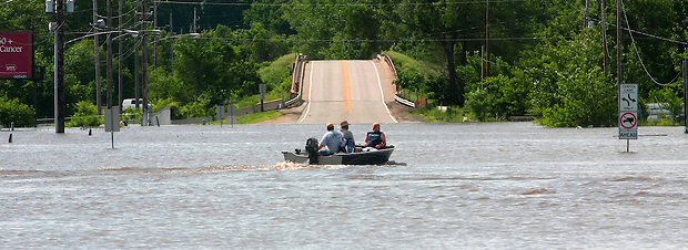 A boat navigates NW Beaver Drive Friday, June 13, 2008 in Johnston.  About four feet of water from the flooded Beaver Creek covers NW Beaver Drive.