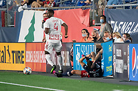 FOXBOROUGH, MA - MAY 22: Andres Reyes #4 of New York Red Bulls tackles Matt Polster #8 of New England Revolution who crashes into the boards during a game between New York Red Bulls and New England Revolution at Gillette Stadium on May 22, 2021 in Foxborough, Massachusetts.