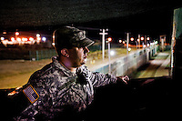 A guard works the night shift in the watchtower of Camp Delta at the American naval base at Guantanamo Bay, where over 600 alleged al Qaeda members have been held indefinitely. Described by the US as 'unlawful enemy combatants', they were captured primarily in Afghanistan during the 'war against terror'.