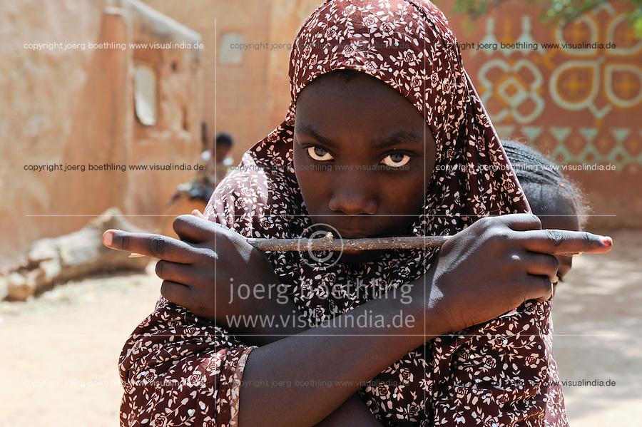 NIGER Zinder, old Haussa town, young girl holding stick / NIGER Zinder, Altstadt Viertel in Haussa Bauweise, junge Frau