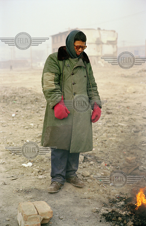 A coal seller warms himself by a fire.  He spends his days distributing coal to various shops and homes in the area.  Shanxi is the largest producer of coal in China.