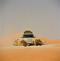 4x4 Landrover Discovery driving through a mixture of volcanic ash and sand, Sahara desert, Libya