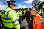 © Joel Goodman - 07973 332324 . 08/05/2011 .  Ellesmere Port, UK . A wall of police separate protesters , including protest organiser IAN CHARLESWORTH , from the Stanlow Oil Refinery entrance . An attempted blockade of Stanlow Oil Refinery at Ellesmere Port , Cheshire , in protest at the price of fuel . Organiser Ian Charlesworth says that a 24 pence discount off the price of a litre of petrol is required to bring the UK in line with average European pricing and to keep British businesses competitive . Photo credit : Joel Goodman