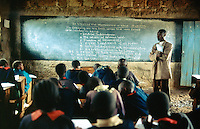Kenya. Rift Valley Province. Mwenja. Primary school. Classroom. Students, girls and boys, listens to their teacher's lesson on kenyan historical struggle for indepence.The arms are laid on a wood desk . The pupils are wearing a green and orange uniform. © 2004 Didier Ruef
