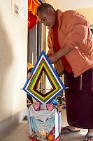 Bodhnath, Nepal.  Tibetan Buddhist Monk Tending to a Buddhist Shrine.