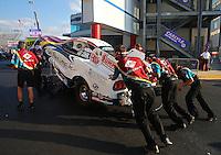 Sep 13, 2013; Charlotte, NC, USA; Crew members push the car of NHRA funny car driver Tim Wilkerson during qualifying for the Carolina Nationals at zMax Dragway. Mandatory Credit: Mark J. Rebilas-