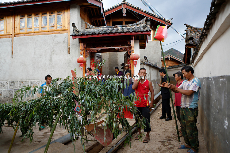 Wumu Village, Yulong County, Yunnan Province, China - Dongba priest He Jixian of the Naxi ethnic group and villagers perform during a rain ceremony to invoke rain amidst current inclement weather, June 2019