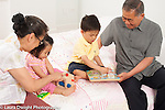 Grandparents playing separately with 18 month old toddler girl and 3 year old preschool age boy playing with toys