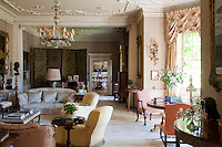 The grand drawing room is comfortably furnished and features a decorative plasterwork ceiling