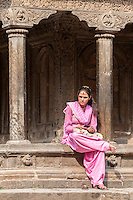 Nepal, Patan.  Young Nepali Woman Sitting on Edge of Temple, Tika on her Forehead, Cell Phone in her Hands.