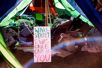 A man sleeps in a tent at the OccupyBoston encampment in Dewey Square in the Financial District in downtown Boston, Massachusetts, USA. The protesters are part of  OccupyBoston, which is part of the OccupyWallStreet movement, expressing discontent with the socioeconomic situation of the 99% of the US population who are not wealthy.  Protestors have been camping in Dewey Square since Sept. 30, 2011. Gradually, larger organizations, including major labor unions, have expressed their support for the OccupyBoston effort.