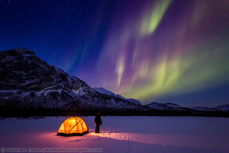 Man watches the aurora overhead from a tented camp in Alaska's Brooks Range.