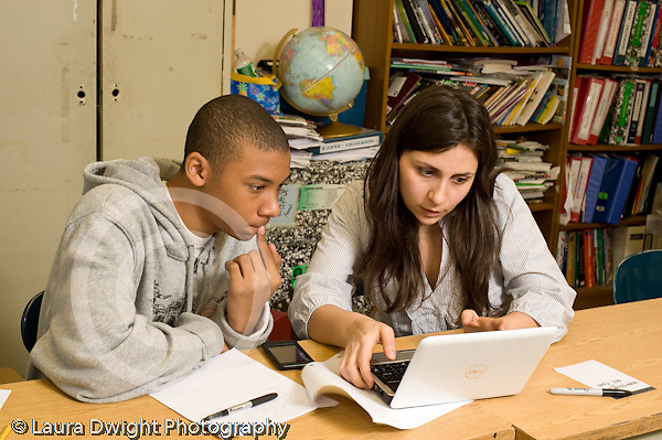 Public Middle School Grade 8 female humanities teacher looking at male student's work on laptop horizontal