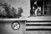Switzerland. Geneva. An old man holds his bicycle before entering the building. He wears a mask on his face to protect himself from the Coronavirus (also called Covid-19). A traffic sign forbids any bicycles, moped or motorcycles to park on the sidewalk. The traffic sign has been misplaced. 15.05.2020 © 2020 Didier Ruef