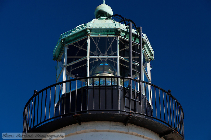 A close-up view of the lantern room and its attached black-painted balcony seen from beneath.  The lantern room appears to be towering above the viewer, and the details on the lantern room's green (copper?) roof are easily visible.  For instance, the room can be seen to have lion or gargoyle figureheads at each of the room's 10 corners, and above each window is a cut-out pattern in the roof's edging of what look to be waves heading towards each other with the cutouts themselves appearing to be horns.   A black ladder climbs to the top of the copper roof, reading the large dome on top.  The white, black, and green building contrast beautifully with the dark blue sky. The lighthouse is in Cabrillo National Monument near San Diego, CA.  I have another version of this same view that is less cropped, if you want.