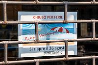 """Milano, cartello di chiuso per ferie (""""buone vacanze"""" con spiaggia, sole, mare e ombrellone) sulla serranda abbassata di un negozio --- Milan, closed for vacation sign (""""happy holidays"""" with sun, sea, beach and umbrella) on the closed shutter of a shop"""