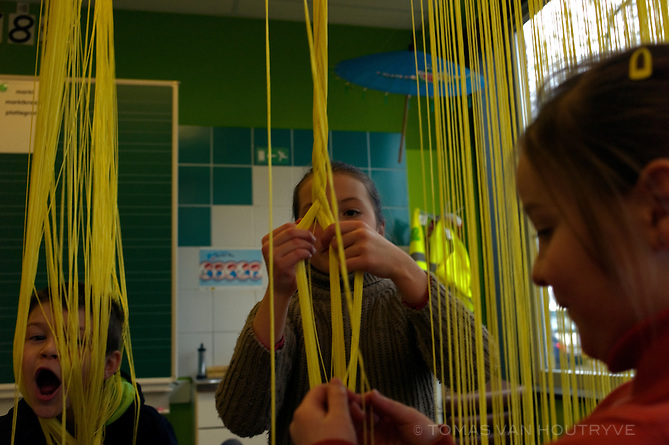 Children play with yellow strings inside a classroom at the Taalkoffer primary school in Comines, Belgium on March 1, 2013. The Taalkoffer is a Dutch language school located inside the French-speaking region of Wallonia. It caused an uproar in 1980 when it was founded.