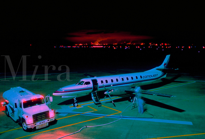 Night shot of commuter plane being refueled, glow of factory lights in background