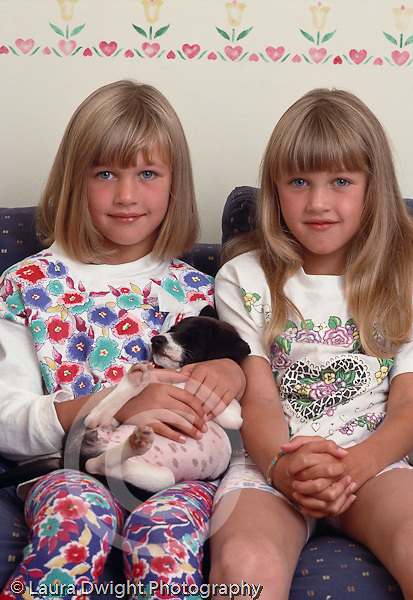 8 year old twins portrait, closeup with pet puppy sitting different clothes and hair styles vertical