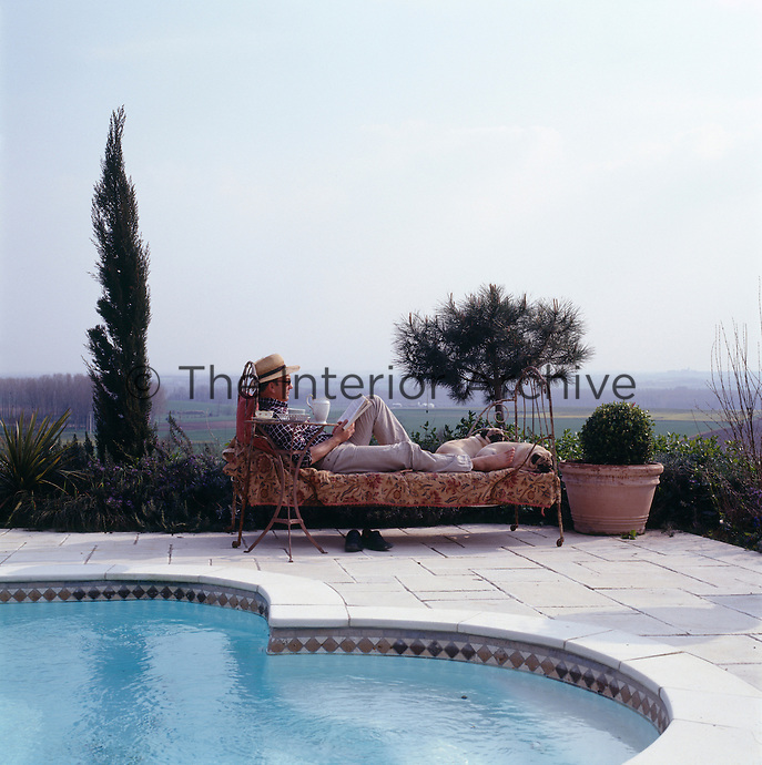 David Hare with his Pugs admires the view from a sunlounger beside the pool
